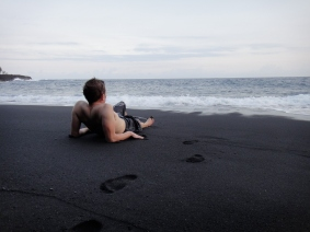 Contemplating my navel, as I stare at the ocean on the black sand. Awesome.